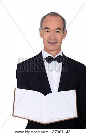 mature waiter holding out menu