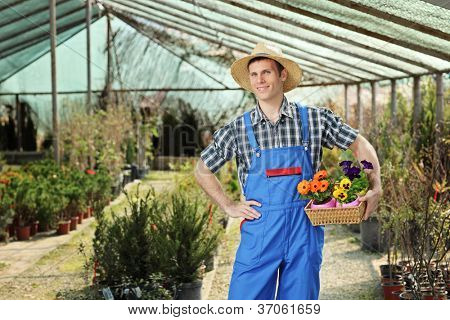 Young worker holding a basket full of flower pots and posing in a garden
