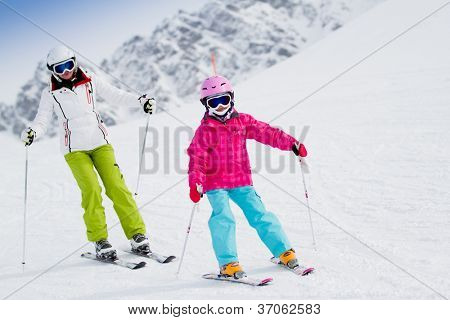 Skiing, winter, ski lesson - kid with mother on mountainside