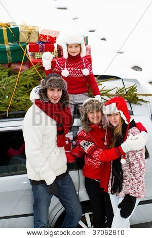 Merry Christmas  - the family is carrying  Christmas tree and gifts on the roof of the car