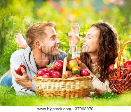 Happy People Eating Healthy Organic Apples in Autumn Garden.Healthy Food.Outdoors.Park.Basket of Apples.Harvest concept .Smiling Couple Relaxing on Grass