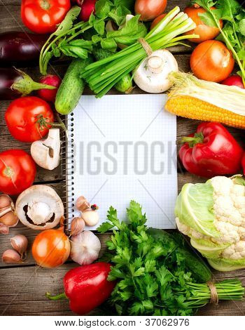 Fresh Organic Vegetables and Spices on a Wooden Background and Paper for Notes. Open Notebook and Fresh Vegetables Background.Diet.Dieting.Space For Your Text