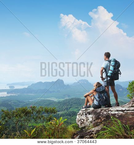 Young backpackers relaxing on top of a mountain and enjoying a valley view