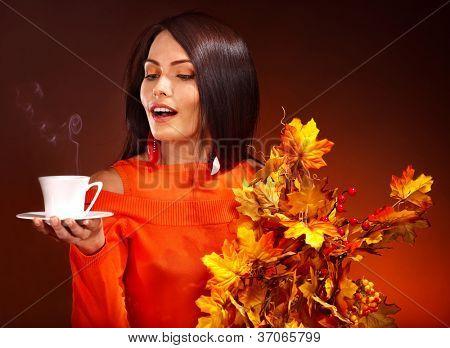 Woman holding Tasse Kaffee und orange Blätter.