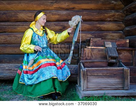 ULAN-UDE, RUSSIA - SEPTEMBER 13:  Unidentified women in traditional Russian dress spinning yarn. Costume show at Baikal Economic Forum, September 13, 2012 in Ulan-Ude, Buryatia, Russia
