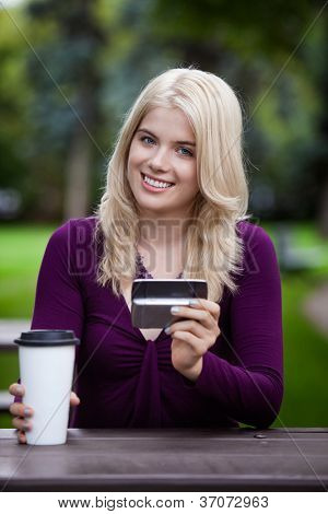 Portrait of a happy smiling college student sitting in park with cell phone and coffee