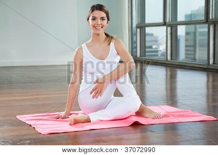 Full length of a happy young woman in Half Spinal Twist pose on mat