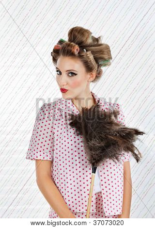 Portrait of young woman with hair curlers puckering while holding an ostrich feather duster
