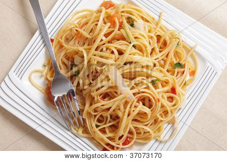 Linguine pasta tossed in a sauce of olive oil, tomato, garlic and basil and topped with slivers of parmesan cheese