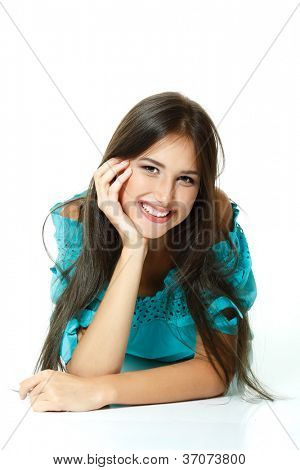 Beautiful teen girl lying down and happy smiling. Isolated on white background