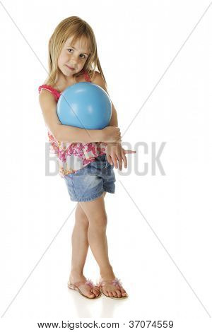 A beautiful young elementary girl shyly cradling a blue playground ball.  On a white background.