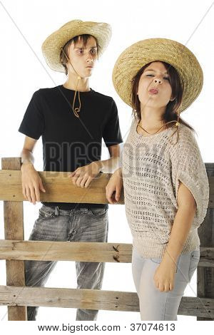 A teen farm girl making a nasty face at the viewer while her boyfriend looks on disapprovingly from behind a rail fence.  On a white background.