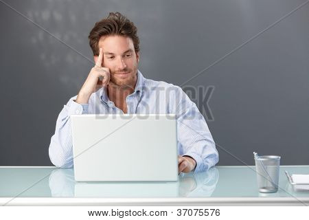 Smiling handsome male office worker sitting at desk looking at laptop computer screen.