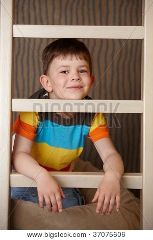 Little boy playing behind ladder, smiling, looking at camera.