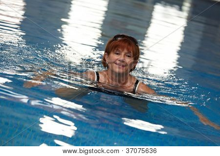 Señora madura activa nadando en la piscina, sonriendo.