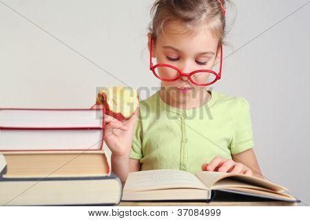 Buch in der Nähe von Stapel Bücher lesen Mädchen in Gläsern Apfel, Essen