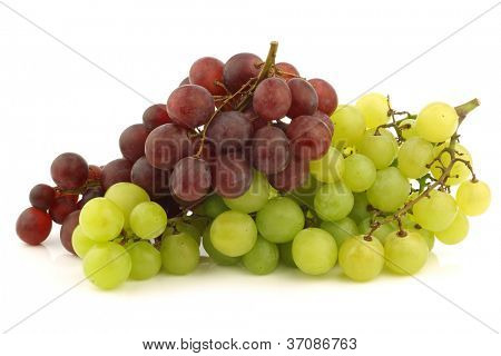fresh red and white seedless  grapes on the vine on a white background
