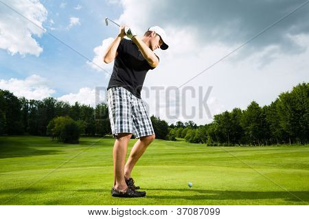 Young golf player on course doing golf swing, he presumably does exercise
