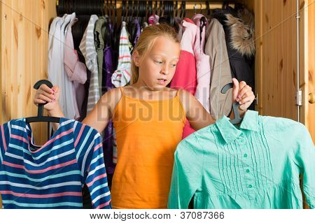 Family - child or teenager in front of her closet or wardrobe and looking for outfit
