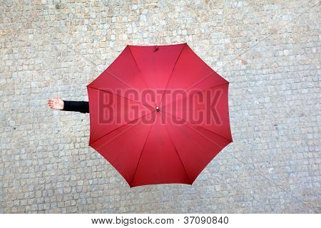 Business woman hidden under umbrella and checking if it's raining