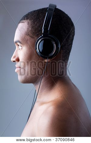 Young black man listening to music in headphones