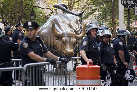 NEW YORK - SEPT 17: Police guard the bronze Charging Bull sculpture on Broadway in Bowling Green Park on the 1yr anniversary of the Occupy Wall St protests on September 17, 2012 in New York City, NY.
