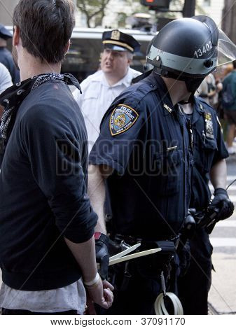 NEW YORK - SEPT 17: A policeman holds the on to a suspect after arresting the unidentified man on the 1yr anniversary of the Occupy Wall St protests on September 17, 2012 in New York City, NY.