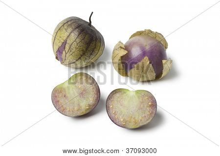 Fresh whole and half tomatillos in their husk on white background