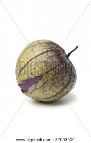 Fresh purple tomatillo in a husk on white background