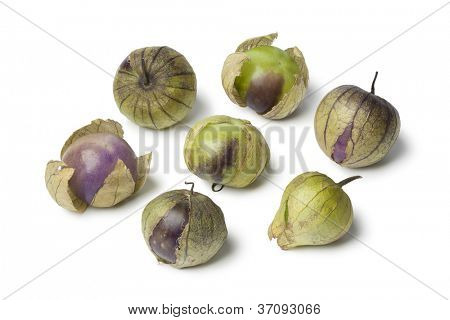 Fresh purple and green tomatillos on white background