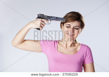 Stressed woman with a gun pointing to his head
