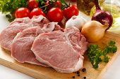 image of bloody  - Raw pork on cutting board and vegetables - JPG