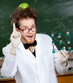 image of mad scientist  - Mad scientist with a green apple on his head shows forefinger while handing molecular	model - JPG