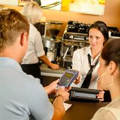 Man paying with credit card at cafe woman service cashier