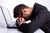 stock photo of boredom  - Tired business man with head and hands down on laptop - JPG