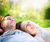 stock photo of orchard  - Happy Smiling Couple Relaxing on Green Grass - JPG