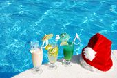 image of santa claus hat  - Santa hat and cocktails near the swimming pool - JPG