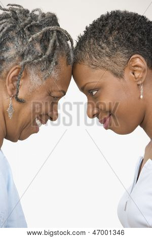 Close up profile of mother and daughter touching forehead