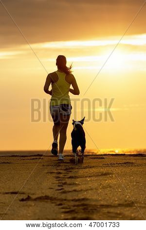 Woman And Dog Running On Sunset