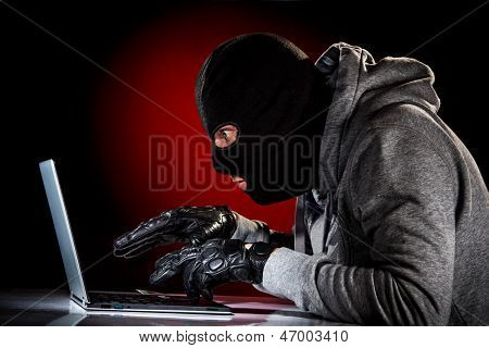 Hacker in a mask with laptop.