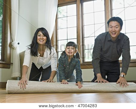 Family unrolling a rug in empty room