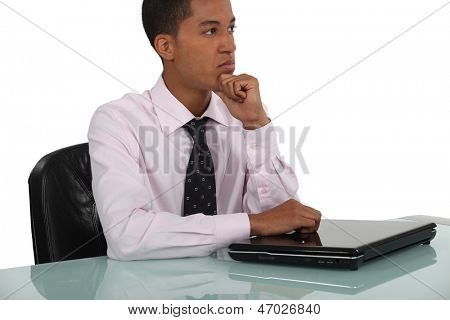 Thoughtful businessman leaning on a closed laptop