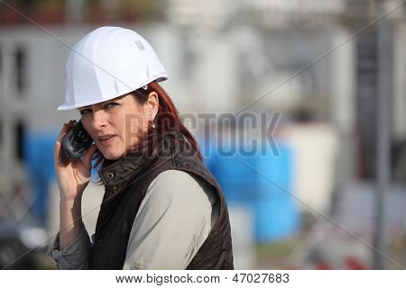Female construction worker on site with a phone