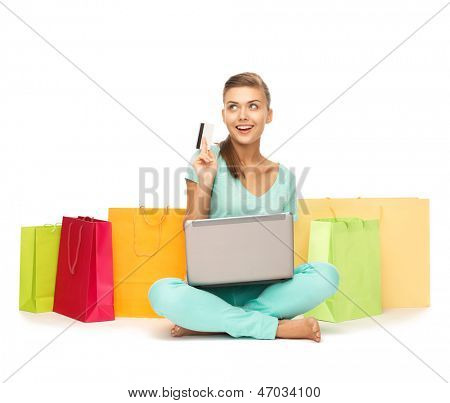 woman with laptop, shopping bags and credit card