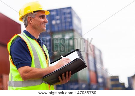 smiling middle aged harbor worker at container depot