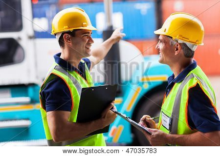 cheerful young harbor worker pointing the forklift while talking to his colleague