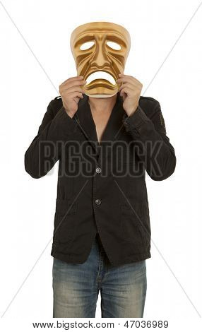 A man holds a golden theatrical mask of tragedy