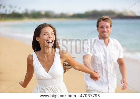 Beach couple running having fun laughing together during summer travel vacation holiday on beautiful golden beach. Joyful excited multi-ethnic couple, Asian woman and Caucasian man.