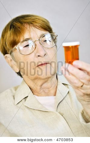 Elderly Woman Reading Pill Bottles