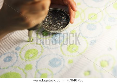 Woman glueing sequins to colorful fabrics